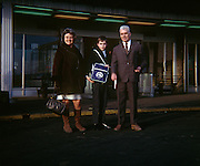 Portrait of parents and their young son standing at Zaventem Brussels airport in the 1970s. Dressed for winter and holding a holiday flight bag with the emblem of their tour to Mexico, the trio stand outside the terminal building of Brussels Zaventem airport in 1970. The picture shows us a memory of nostalgia in an era from the last century.