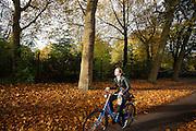 In Utrecht rijden fietsers langs het Julianapark waar de bomen mooie herfstkleuren hebben. Een meisje eet haar boterhammen terwijl ze fietst.<br /> <br /> In Utrecht cyclists pass the Juliana park with trees in autumn colors.