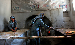 KABUL,AFGHANISTAN - SEPT. 10:  Afghan widows make bread in a bakery set up to help vulnerable families by subsidizing the cost of bread in Kabul, Afghanistan September 10,2002. (Photo by Ami Vitale/Getty Images)