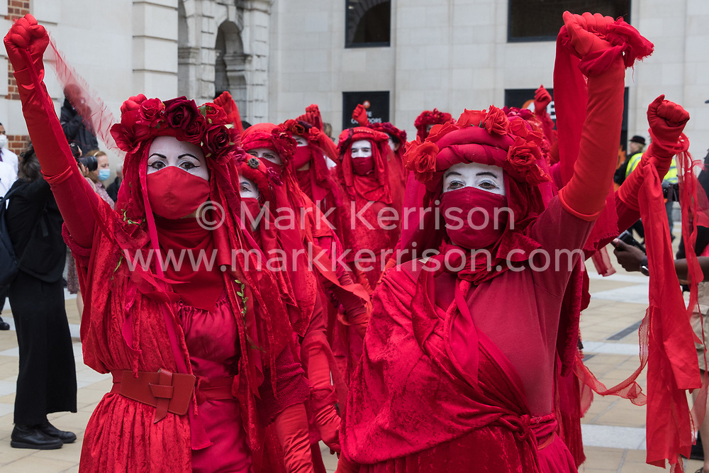 London, UK. 27th August, 2021. Members of the Extinction Rebellion Red Rebel Brigade raise clenched fists as they arrive in Paternoster Square following a Blood Money March through the City of London on the fifth day of Impossible Rebellion protests. Extinction Rebellion were intending to highlight financial institutions funding fossil fuel projects, especially in the Global South, as well as law firms and institutions which facilitate them, whilst calling on the UK government to cease all new fossil fuel investment with immediate effect.