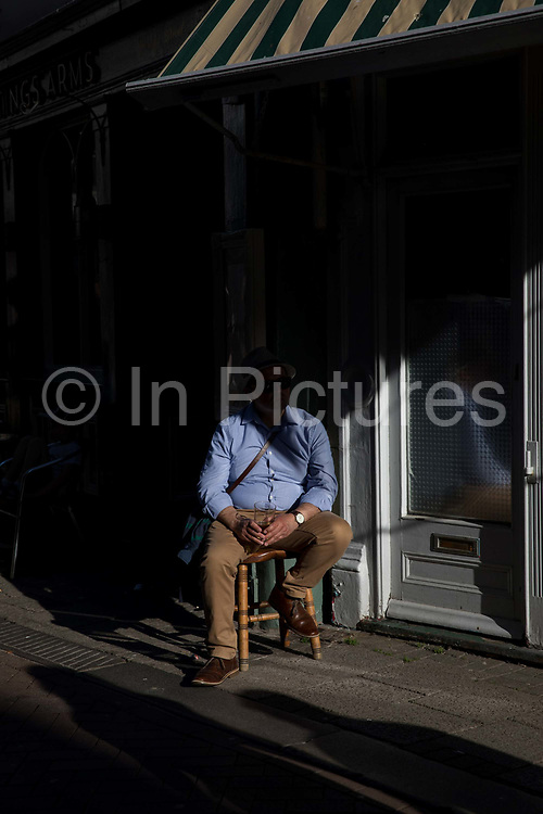 A man sitting in a shadow drinking a pint of beer in the historic old town of Hastings on the 20th April 2019 in Hastings in the United Kingdom. Hastings is a town on England's southeast coast, its known for the 1066 Battle of Hastings.
