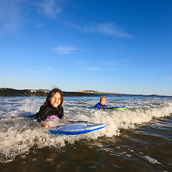 A brother and sister (ages 6 and 8) boogie boarding at Popham Beach State Park in Phippsburg, Maine.