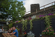 Locals residents sitting in the Pig and Whistle pub opposite the burnt shell of Grenfell on the 16th June 2017 in North Kensington, London, United Kingdom. The Grenfell Tower fire occurred on 14th June 2017 at the 24-storey block of public housing flats in North Kensington, West London. It caused at least 80 deaths and over 70 injuries, yet the actual numbers have yet to be confirmed