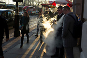 Two men simultaneously exhale clouds of vape smoke in winter sunshine on Piccadilly, on 20th January 2020, in London, England.