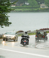 """A wet """"Welcome to the Lake"""" as motorcyclists arrive into Weirs Beach for the beginning of Laconia's  Motorcycle Week Friday evening.  (Karen Bobotas/for the Laconia Daily Sun)"""