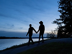 United States, Washington, Bellevue, couple walking along shore of Lake Washington at dusk (silhouette)
