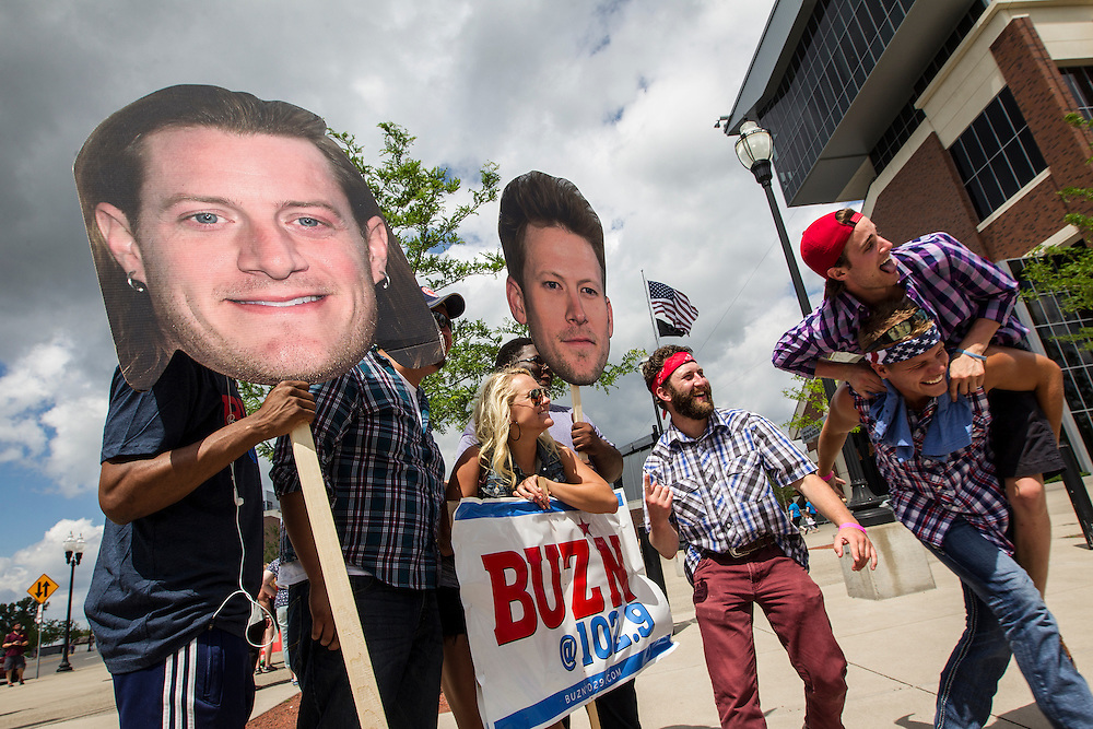 BUZN 102.9FM volunteers hold the heads of Florida Georgia Line band members on sticks for fans to pose with before the Luke Bryan Kick The Dust Up Tour at TCF Bank Stadium in Minneapolis June 20, 2015.