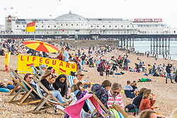© Licensed to London News Pictures. 28/07/2019. Brighton, UK. Members of the public take advantage of the mildest weather to spend time on the beach in Brighton and Hove. Photo credit: Hugo Michiels/LNP