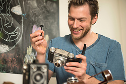 Man repairing antique camera in dining room, Munich, Bavaria, Germany