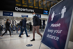 © Licensed to London News Pictures. 07/09/2020. London, UK. Passengers at Waterloo Station pass a sign saying 'Please keep your distance'. Train capacity is supposed to reach 90% today as holidays come to an end and schools return. Photo credit: Peter Macdiarmid/LNP