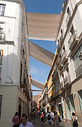 Fabric spread over buildings to provide shade in busy shopping street Mendez Nunez in central Seville, Spain