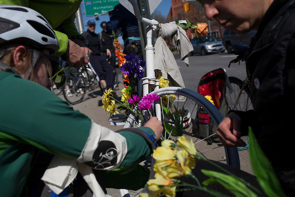 Families and friends of New Yorkers killed while bicycling on New York City streets gather at an unnamed Ghost Bike memorial near the corner of Borden and Greenpoint Aves in Queens, NY, on Sunday, April 21, 2013 as they participate in the 8th Annual Ghost Bike Memorial Ride. The ride visited the 20 white-painted Ghost Bikes installed at the scene of bicyclist fatalities in five boroughs before converging at the intersection of Queens Boulevard and Jackson Avenue to dedicate a memorial to all of the cyclists who were killed in traffic crashes in 2012 whose deaths did not make the news...According to the New York City Department of Transportation, 136 pedestrians and 18 bicyclists were killed in 2012. In 2011, 134 pedestrians and 22 bicyclists were killed on New York City streets. To date, at least two bicyclists have been killed in 2013...Photograph by Andrew Hinderaker for the Ghost Bike Project.