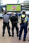 A couple of railway security guards and a policeman watch the 2008 Rugby League Grand Final on a big screen set up outside the Olympic Stadium. Sydney, Australia