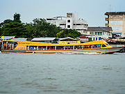 20 JULY 2015 - BANGKOK, THAILAND:   A commuter boat brings people into Bangkok from suburbs north of the city past housing on the Chao Phraya River south of Pin Klao Bridge and the planned redevelopment of the riverfront. The Chao Phraya promenade is development project of parks, walkways and recreational areas on the Chao Phraya River between Pin Klao and Phra Nang Klao Bridges. The 14 kilometer long promenade will cost approximately 14 billion Baht (407 million US Dollars). The project involves the forced eviction of more than 200 communities of people who live along the river, a dozen riverfront  temples, several schools, and privately-owned piers on both sides of the Chao Phraya River. Construction is scheduled on the project is scheduled to start in early 2016. There has been very little public input on the planned redevelopment.         PHOTO BY JACK KURTZ
