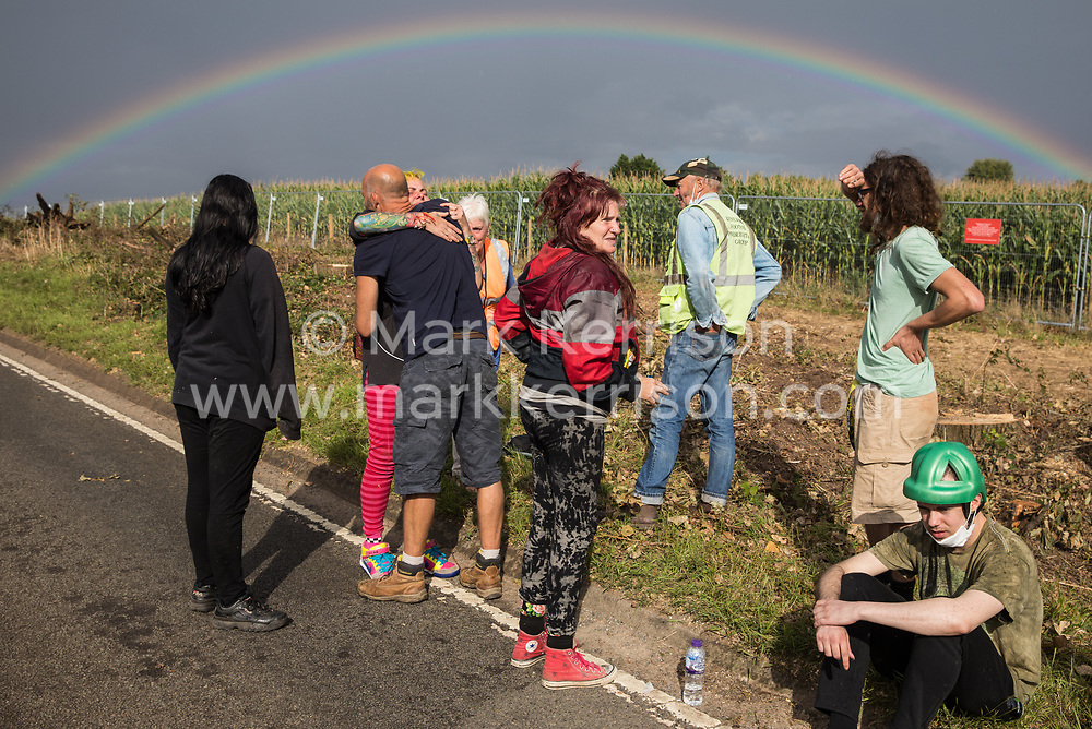 Anti-HS2 activists console each other in front of a rainbow alongside the Fosse Way after attempting to protect a mature oak tree from felling in connection with the HS2 high-speed rail link on 24th August 2020 in Offchurch, United Kingdom. The controversial HS2 infrastructure project is currently expected to cost £106bn and will destroy or significantly impact many irreplaceable natural habitats, including 108 ancient woodlands.