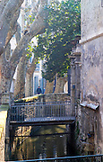 A small street with a canal in the old town, bridges, trees and a man walking, Avignon, Vaucluse, Rhone, Provence, France