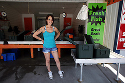 07 May 2010. Westwego, Louisiana. <br /> Ashley Palmisano, a 22 year old single mother of two sells shrimp from A&B's seafood at the Westwego Fish market just outside New Orleans. Ashley worries that she may not have a job to go to in a couple of weeks. All seafood prices have risen 25% in the past 7 days alone as stocks run low thanks to closed fishing grounds affected by oil pollution. Today was the opening day of the inshore shrimp season. The season was closed before it could open thanks to BP's disastrous environmental catastrophe out in the Gulf of Mexico. Approximately 210,000 barrels of oil per day is leaking uncontrollably into the Gulf because of the explosion and collapse of the Deepwater Horizon drilling platform 46 miles out to sea. The closure of fishing grounds both east and west of the Mississippi river outflow is crippling thousands of local fishermen and all affiliated businesses and families who rely on the seafood industry. None of the shrimp or other seafood offered at the market are fresh catch from today. Everything has been through the IQF (Instant Quick Freeze) process and is seafood caught earlier in the season and brought from storage freezers in Venice and Grand Isle. Stocks are running low. With no new catches, the market will be forced to rely on farmed shrimp shipped in from Texas and Georgia. Local traders refuse to stock Chinese import fish raised with growth hormones, pesticides, fungicides and other contaminants widely found in Chinese farm raised seafood. Many fear losing their jobs and everything they own as a result of BP's Gulf Coast environmental disaster.<br /> Photo credit; Charlie Varley/varleypix.com