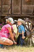 A young cowboy rests on a wagon wheel during Cheyenne Frontier Days July 25, 2015 in Cheyenne, Wyoming. Frontier Days celebrates the cowboy traditions of the west with a rodeo, parade and fair.