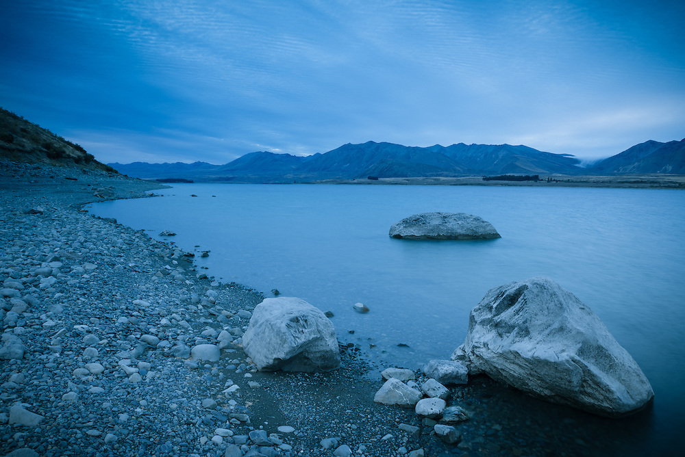 Lake Tekapo at dusk with rock formations and still water