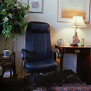 A black leather chair with wooden arm rests and a comfort control on the front face of right arm, on an oriental carpet, with a budha base lamp and orginal art on the wall behind it, a large tree to the left illuminated by a window.