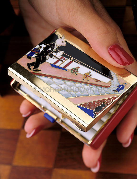 Art Deco Cigarette case in woman's hand. Art Deco enamel and gold box of tuxedo-clad bunny rabbit serving martinis in a Paris cake by Raymond Yard