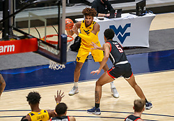 Jan 25, 2021; Morgantown, West Virginia, USA; West Virginia Mountaineers guard Miles McBride (4) passes the ball while defended by Texas Tech Red Raiders guard Micah Peavy (5) during the first half at WVU Coliseum. Mandatory Credit: Ben Queen-USA TODAY Sports