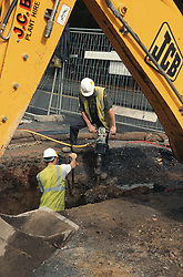 Workmen digging trench using pneumatic drill and JCB,