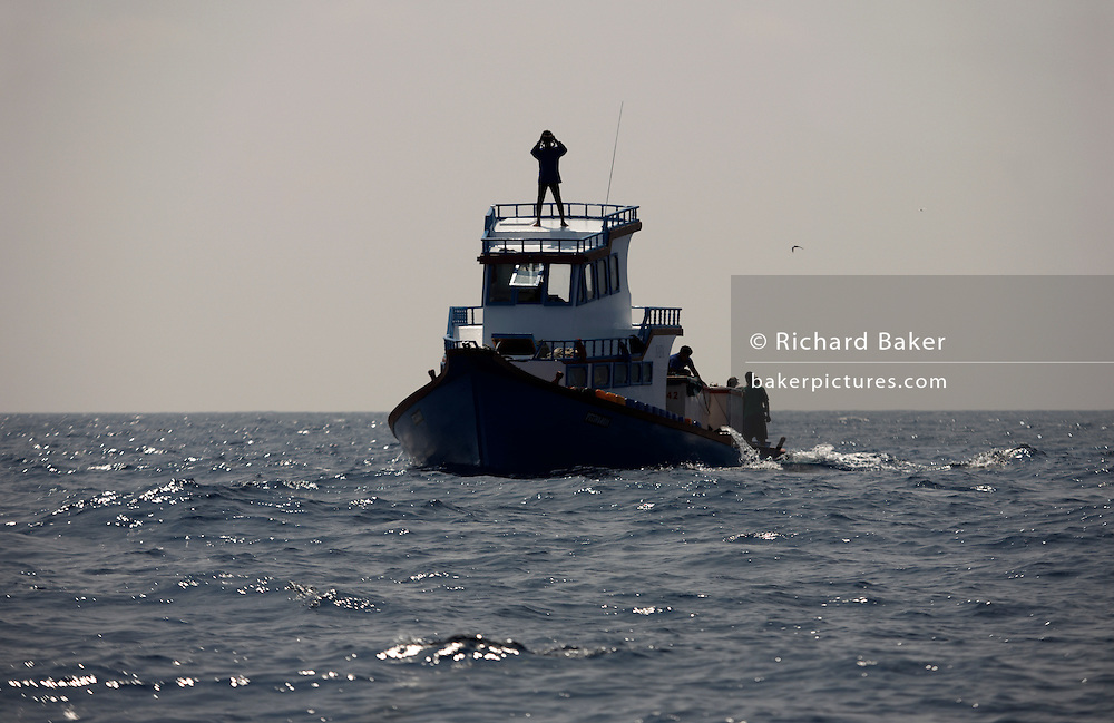 A lookout scans the horizon for tuna fish aboard a traditional Maldivian dhoni fishing boat on calm waters of the Indian Ocean