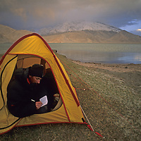 Mark Newcomb (MR) writes in his journal in a camp by Lake Karakul in the Pamir Mountains of Xinjiang, China.