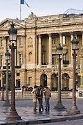 Tourists talking on street corner in front of Hotel de Crillon in Place de la Concorde, Central Paris, France