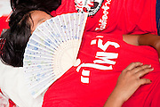 17 APRIL 2010 - BANGKOK, THAILAND: People sleep with small hand fans over their faces. A whole economy has sprung up around the Red Shirt camp with vendors selling everything from snacks and meals to mats (that they sit on) to fans, hats and Red Shirt souvenirs. The Red Shirts continue to occupy Ratchaprasong Intersection an the high end shopping district of Bangkok. They are calling for Thai Prime Minister Abhisit Vejjajiva to step down and dissolve the parliament. Most of the Red Shirts support ousted former Prime Minister Thaksin Shinawatra.   PHOTO BY JACK KURTZ