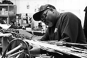 Tommy Bolton grinding a part on a drag racing bike at his shop in Oklahoma City.