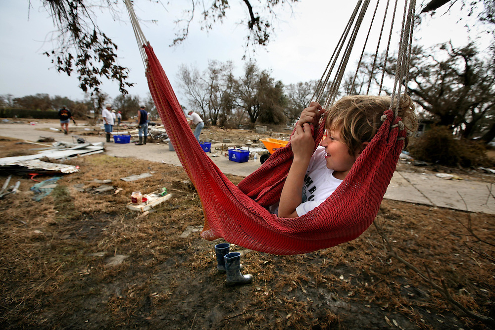 ORG XMIT: *S0424385295* (09/19/08) ---  Cameron Sauer, 9, of Houston takes a break in a hammock while family members help his aunt and uncle retrieve whatever is left on the site where their home stood before Hurricane Ike wiped it off the foundation in Sabine Pass Friday September 19, 2008..09282008xNEWS