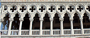 Exterior facade of the Doge's Palace in Venice, Italy. The palace was the residence of the Doge of Venice, the supreme authority of the Republic of Venice. Its two most visible façades look towards the Venetian Lagoon and St. Mark's Square, or rather the Piazzetta. The use of arcading in the lower stories produces an interesting 'gravity-defying' effect. There is also effective use of colour contrasts. largely constructed from 1309 to 1424, designed perhaps by Filippo Calendario. It replaced earlier fortified buildings of which relatively little is known. Giovanni and Bartolomeo Bon created the Porta della Carta in 1442, a monumental late-gothic gate on the Piazzetta side of the palace. This gate leads to a central courtyard. The palace was badly damaged by a fire on December 20, 1577.