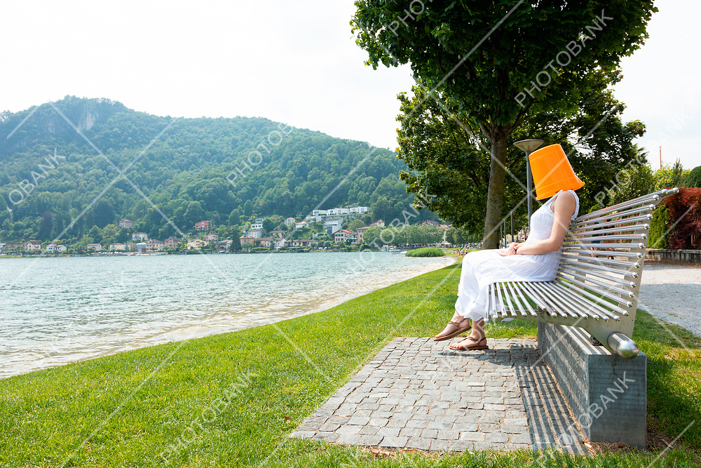 Young woman sitting on a bench by the lake with an orange bucket on her head. He is secretly waiting for something.