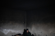 A man from Afghanistan is seen in the morning wrapped in a blanket. Many are living in abandoned building around the town of Bihac, waiting to attempt to cross the Bosnian Croatian border, Bihac January 27, 2021.