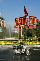 Vietnamese man cruising Saigon on his motorbike, past colorful flags associated with Tet holidays, or Lunar New Year. Tet or Lunar New Year is the most important holiday and festival in Vietnam. It is the Vietnamese New Year based on the Lunar calendar. It takes place from the first day of the first month of the Lunar calendar (around late January or early February) until at least the third day.