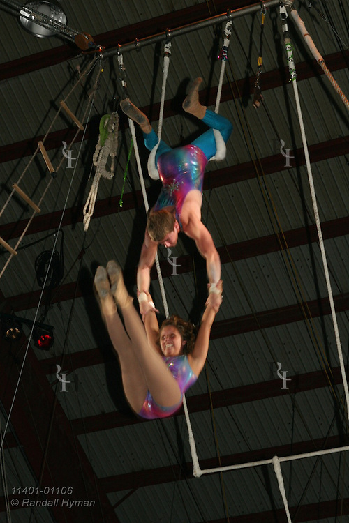 Teen couple performs double trapeze act as boy suspends swinging girl in air at Peru Amateur Circus; Peru, Indiana.
