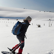 A woman walking on snowshoes in a winter scenery