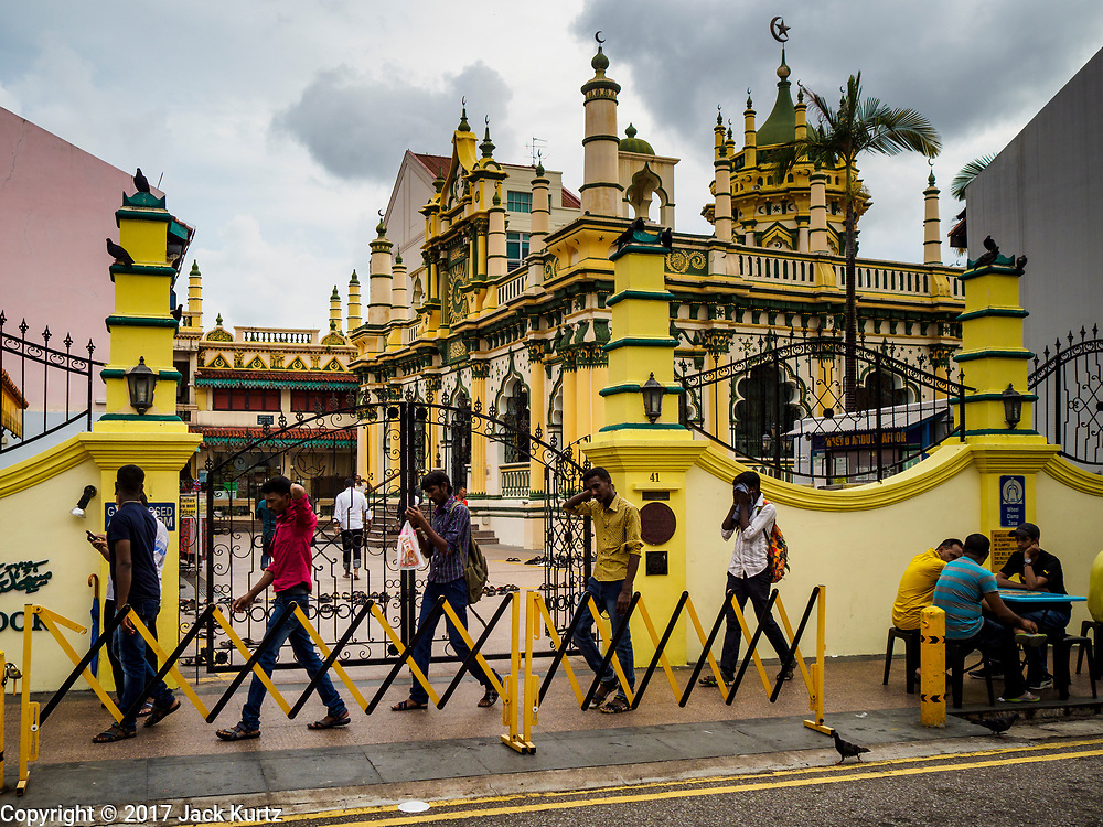"""09 JULY 2017 - SINGAPORE: Guest workers from the Indian sub-continent walk past Abdul Gaffoor Mosque in Singapore's """"Little India."""" There are hundreds of thousands of guest workers from the Indian sub-continent in Singapore. Most work 5 ½ to six days per week. On Sundays, the normal day off, they come into Singapore's """"Little India"""" neighborhood to eat, drink, send money home, go to doctors and dentists and socialize. Most of the workers live in dormitory style housing far from central Singapore and Sunday is the only day they have away from their job sites. Most work in blue collar fields, like construction or as laborers.    PHOTO BY JACK KURTZ"""