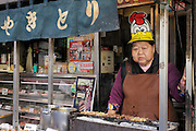 portrait of female street food seller preparing Mitarashi-dango Tokyo Japan