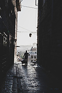A man pushes a dolly late on a summer afternoon down a street in Aleppo, Syria. (June 23, 2010)