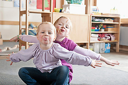 Portrait of two little sisters in kindergarten sticking out tongues