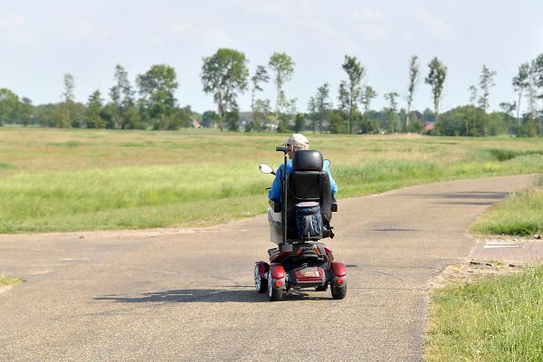 Nederland, Ubbergen, 22-5-2018Man met lichamelijke beperking, handicap, rijdt in haar scootmobiel over een landweg. Foto: Flip Franssen