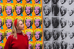 "© Licensed to London News Pictures. 10/03/2020. LONDON, UK. A staff member poses next to ""Marilyn Diptych"", 1962, by Andy Warhol. Preview of ""Andy Warhol"", a retrospective of over 100 works by one of the most recognisable artists of the late 20th century.  The exhibition runs 12 March to 6 September 2020 at Tate Modern.  Photo credit: Stephen Chung/LNP"