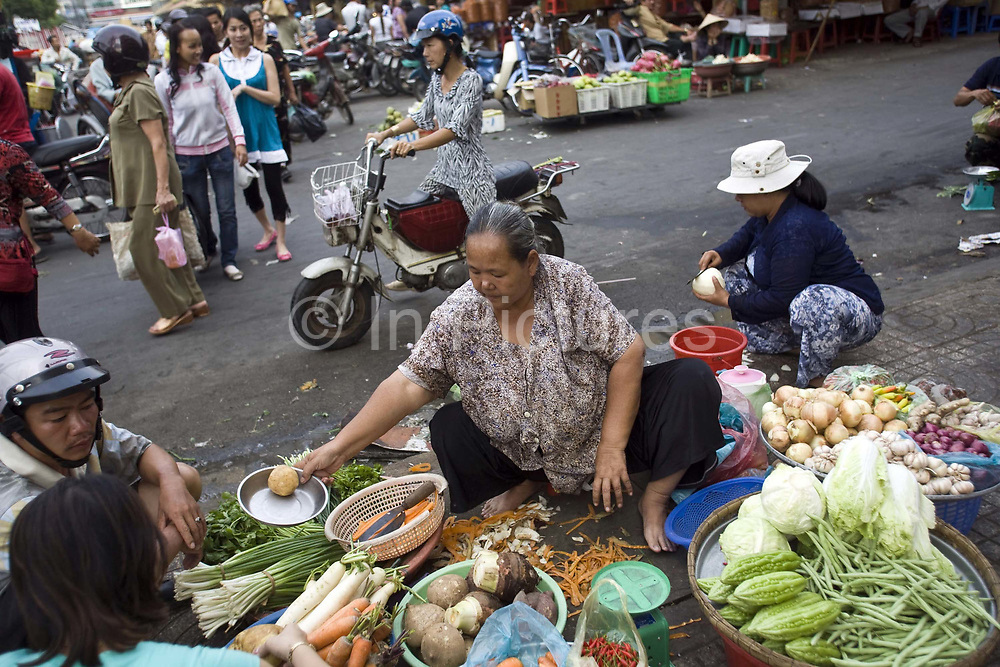 A woman street vendor selling food on the street in Ho Chi Minh City (formerly Saigon), Vietnam