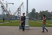 © Licensed to London News Pictures. 01/01/2012. A police officer watches a man using a mobile phone outside Ho Chi Minh's Mausoleum in Hanoi, Vietnam. Photo credit : Stephen Simpson/LNP