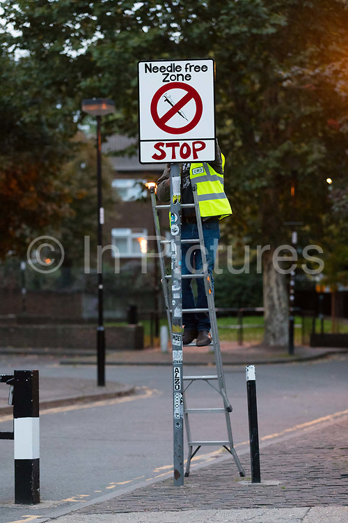 Community activists from the 'Columbia Road Cartel' erect hoax 'Needle free zone' road signs as part of the anti drugs street art campaign in residential streets near Columbia Road in Shoreditch east London on September 16, 2018 to highlight high levels of drug dealing in this part of Tower Hamlets, where the cheapest heroin in Europe can allegedly be purchased. The road signs and markings were commissioned by residents from the Weavers Community Action Group who claim that the police and Tower Hamlets Council are failing to address the growing drugs problem in the area.  (photo by Vickie Flores / In Pictures via Getty Images)