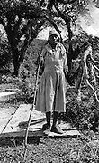 Maroon Elderly Lady standing on her Husbands Grave