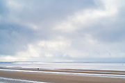 Lone figure walking along sandy beach by the Bristol Channel at Burnham-on-Sea, Somerset, UK